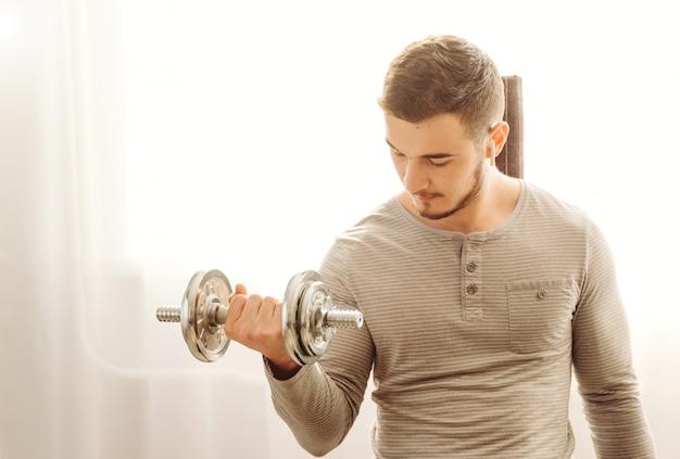 Junger mann, der fitnessübung zu hause tut Kostenlose Fotos