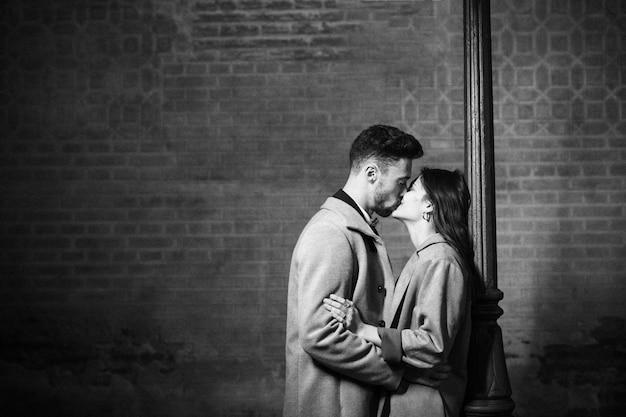 Junger mann, der frau nahe straßenlaterne küsst und umarmt Kostenlose Fotos