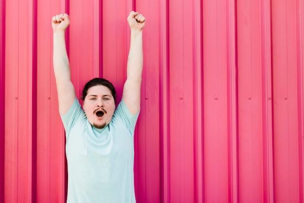 Junger mann, der gegen das rote gewölbte wandzujubeln steht Kostenlose Fotos