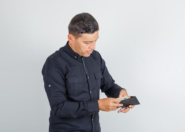 Junger mann, der geld in der brieftasche im schwarzen hemd zählt Kostenlose Fotos