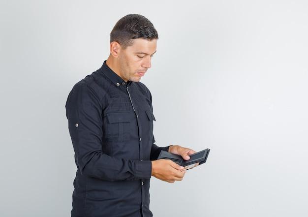 Junger mann, der geld von der brieftasche im schwarzen hemd herausnimmt. Kostenlose Fotos