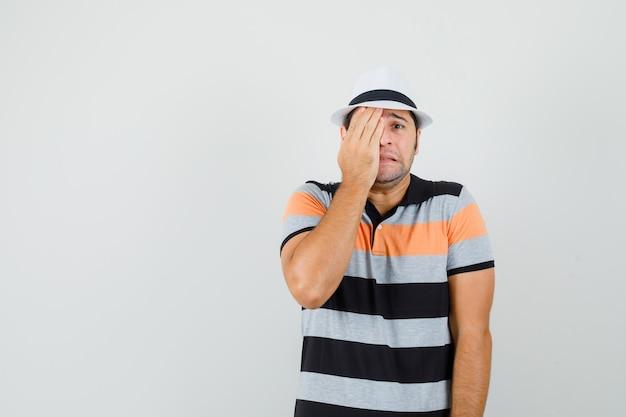 Junger mann, der gesicht mit seiner hand in gestreiftem t-shirt, hut bedeckt und stressigen raum für text sucht Kostenlose Fotos