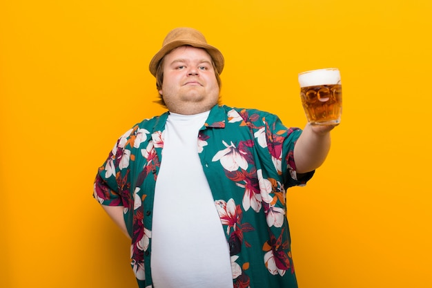 Junger mann der großen größe mit einem halben liter bier flache wand Premium Fotos