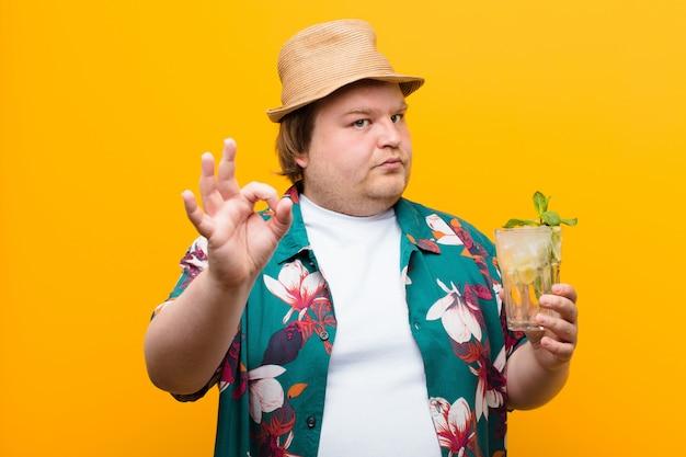 Junger mann der großen größe mit einem mojito getränk gegen flache wand Premium Fotos