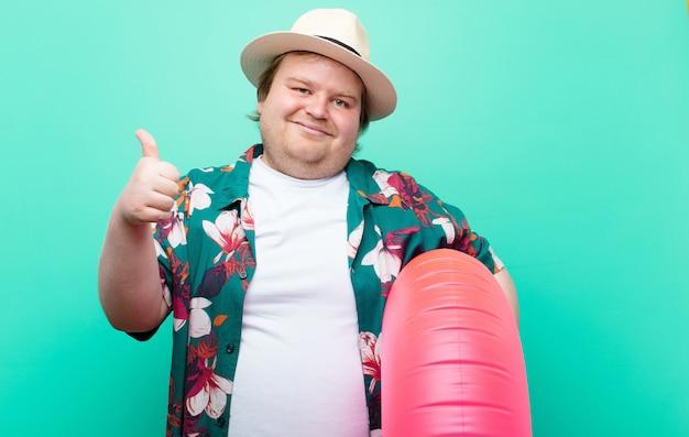 Junger mann der großen größe mit einer flachen wand des aufblasbaren donuts Premium Fotos
