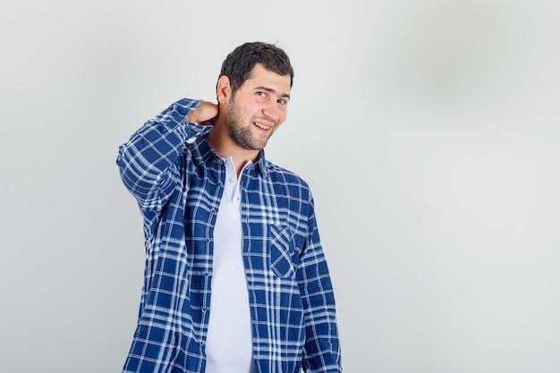 Junger mann, der hand auf seinem hals im hemd hält und fröhlich aussieht. Kostenlose Fotos