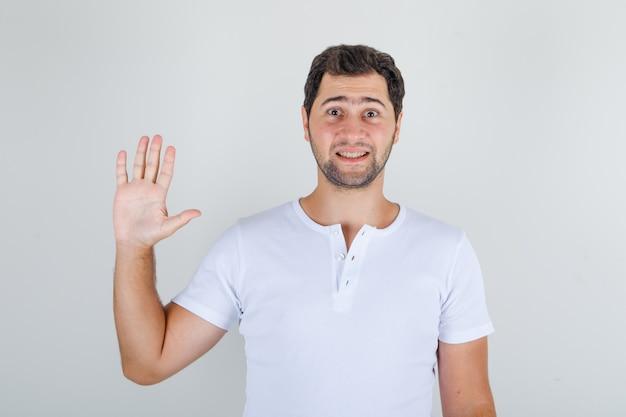 Junger mann, der hand in der hallo-geste im weißen t-shirt winkt und lustig schaut Kostenlose Fotos