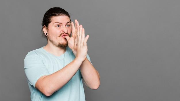 Junger mann, der handtrompetegeste gegen grauen hintergrund macht Kostenlose Fotos