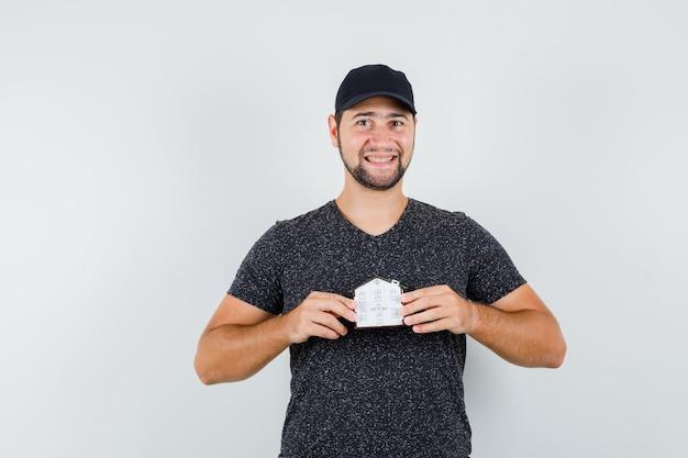 Junger mann, der hausmodell im t-shirt und in der mütze hält und fröhlich schaut Kostenlose Fotos