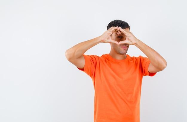 Junger mann, der herzgeste im orange t-shirt zeigt und lustig schaut Kostenlose Fotos