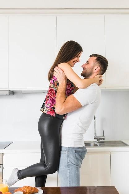 Junger mann, der ihre freundin in der küche trägt Kostenlose Fotos