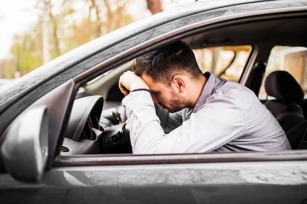 Junger mann, der im auto sehr verärgert und gestresst nach schwerem versagen sitzt und sich im stau bewegt Kostenlose Fotos