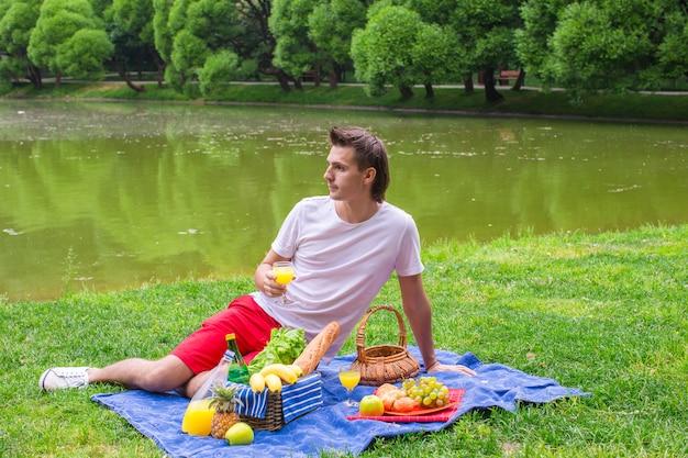 Junger mann, der im park picknickt und sich entspannt Premium Fotos