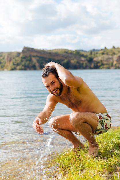 Junger mann, der im wasser auf fluss plätschert Kostenlose Fotos