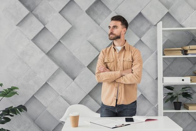 Junger mann, der in einem büro steht Kostenlose Fotos