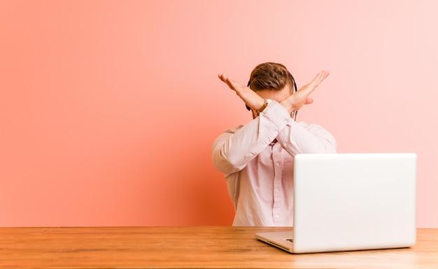 Junger mann, der in einem kundenkontaktcenter hält zwei arme gekreuzt arbeitet Premium Fotos