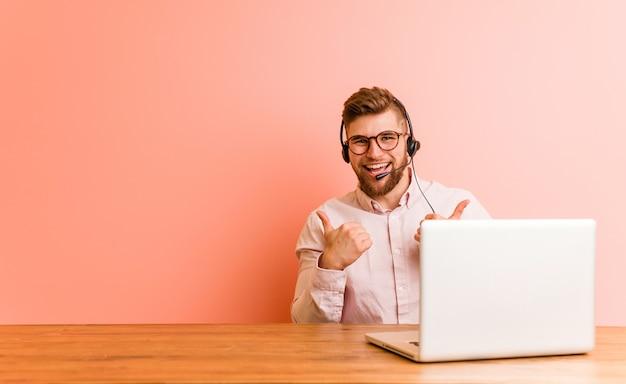 Junger mann, der in einem kundenkontaktcenter oben anhebt beide daumen, lächelt und überzeugt arbeitet. Premium Fotos