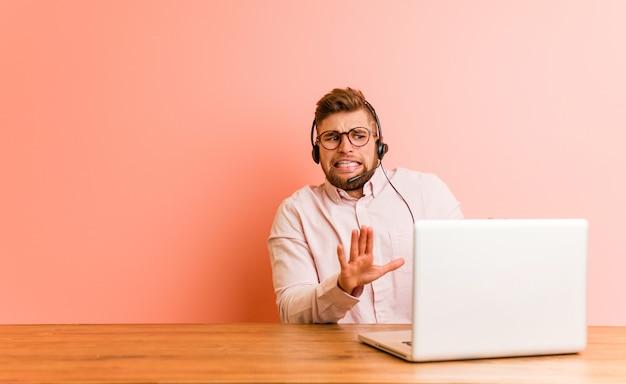 Junger mann, der in einem kundenkontaktcenter zurückweist jemand arbeitet, das eine geste des ekels zeigt. Premium Fotos