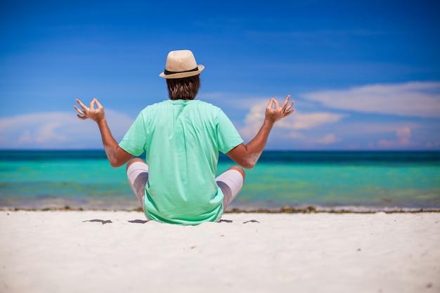 Junger mann, der in lotussitz auf weißem sandstrand sitzt Premium Fotos