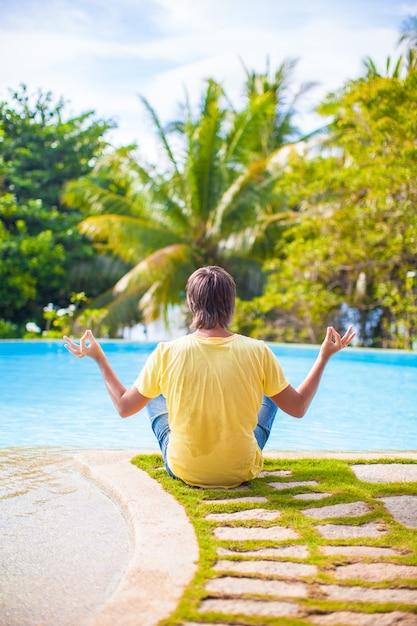 Junger mann, der in lotussitz nahe dem pool sitzt Premium Fotos