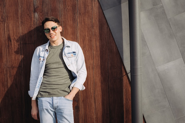 Junger mann, der in seiner sonnenbrille nahe bei der wand aufwirft Premium Fotos