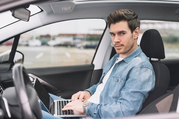 Junger mann, der innerhalb des modernen autos mit dem laptop betrachtet kamera sitzt Kostenlose Fotos
