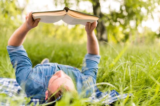 Junger mann, der interessantes buch bei der entspannung im gras liest Kostenlose Fotos