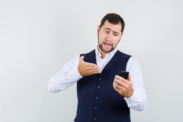 Junger mann, der jemanden verantwortlich auf video-chat im hemd, weste hält Kostenlose Fotos