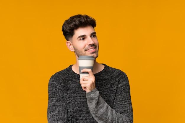 Junger mann, der kaffee hält, um wegzunehmen Premium Fotos