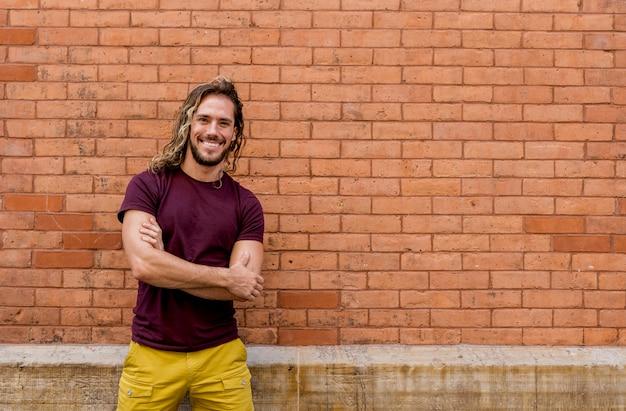 Junger mann, der kamera mit backsteinmauer betrachtet Kostenlose Fotos