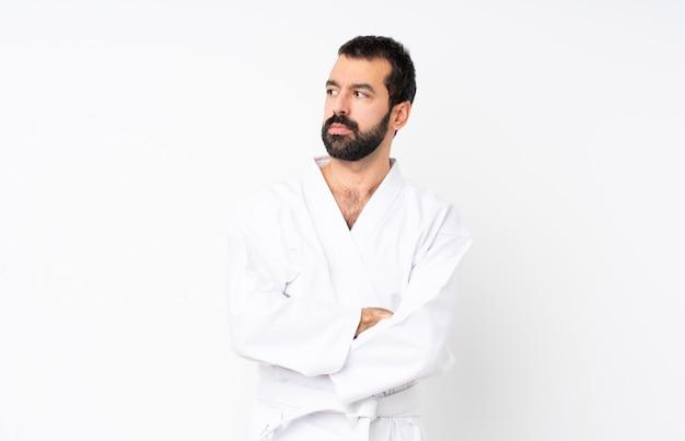 Junger mann, der karate über getrenntem weißem portrait tut Premium Fotos