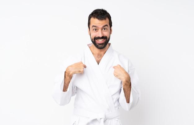 Junger mann, der karate über lokalisiertem weiß mit überraschungsgesichtsausdruck tut Premium Fotos