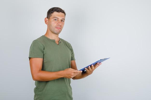 Junger mann, der klemmbrett im armeegrün-t-shirt, vorderansicht hält. Kostenlose Fotos