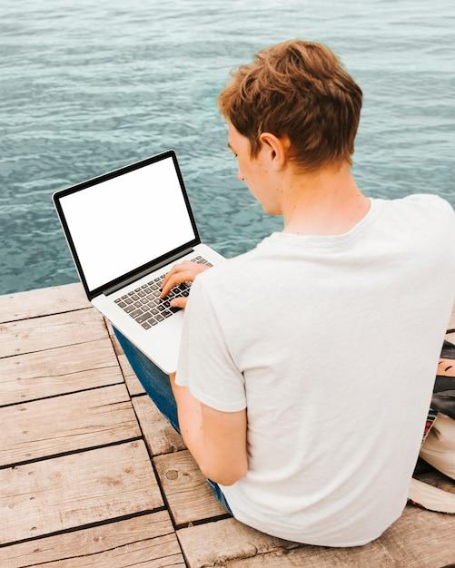 Junger mann, der laptop durch das wasser verwendet Kostenlose Fotos
