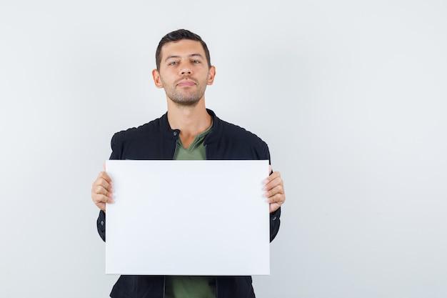 Junger mann, der leeres plakat im t-shirt, in der jacke hält und vernünftig schaut. vorderansicht. Kostenlose Fotos