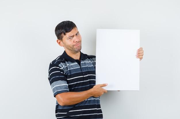 Junger mann, der leeres plakat im t-shirt, vorderansicht hält. Kostenlose Fotos