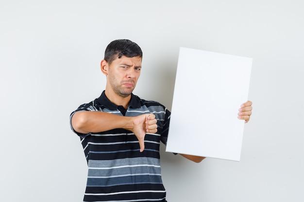 Junger mann, der leeres plakat mit daumen unten im t-shirt hält und gedämpfte vorderansicht schaut. Kostenlose Fotos