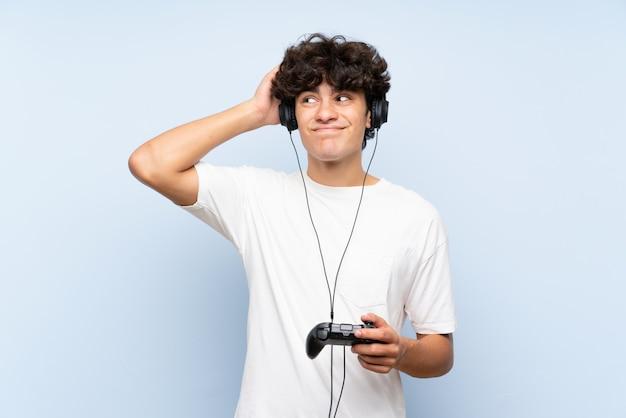 Junger mann, der mit einem videospielprüfer über der lokalisierten blauen wand hat zweifel und mit verwirren gesichtsausdruck spielt Premium Fotos