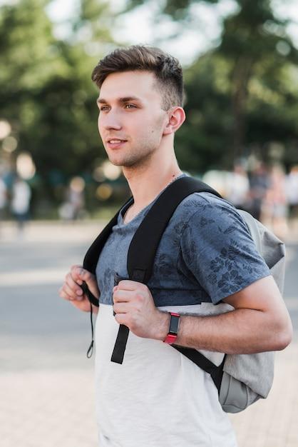 junger mann der mit rucksack steht kostenlose foto