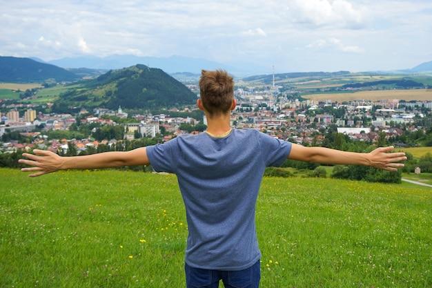Junger mann, der mit seinen händen offen in ruzomberok, slowakei steht Kostenlose Fotos