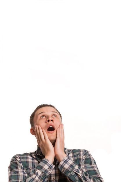 Junger mann, der mit seinen händen zu seinem gesicht erschrocken schaut. erschrocken ein schreien und schaute zu dem kopierraum über ihm auf. emotionen, überwältigendes, schockierendes nachrichtenkonzept Premium Fotos