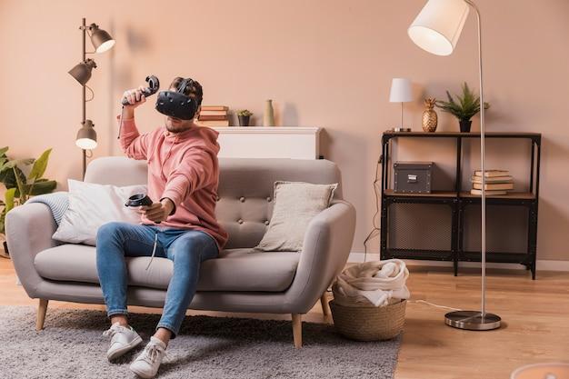 Junger mann, der mit virtuellem kopfhörer spielt Kostenlose Fotos