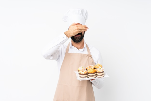 Junger mann, der muffinkuchenbedeckungsaugen durch hände hält. ich will nichts sehen Premium Fotos