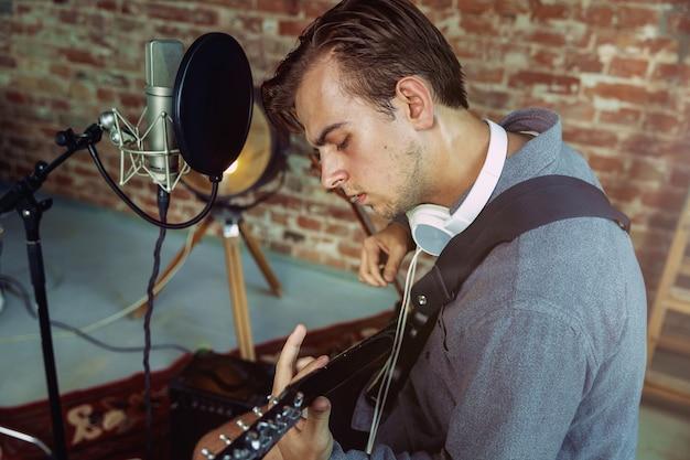 Junger mann, der musik aufzeichnet, gitarre spielt und zu hause singt Kostenlose Fotos