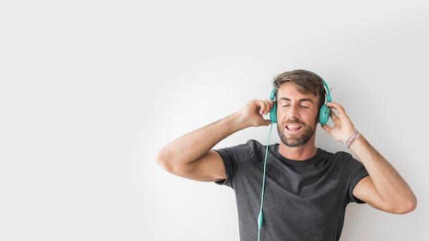 Junger mann, der musik mit kopfhörern genießt Kostenlose Fotos