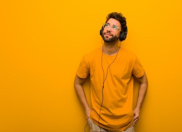 Junger mann, der musik träumt vom erreichen von zielen und von zwecken hört Premium Fotos