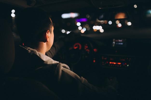 Junger mann, der nachts sein auto fährt Kostenlose Fotos