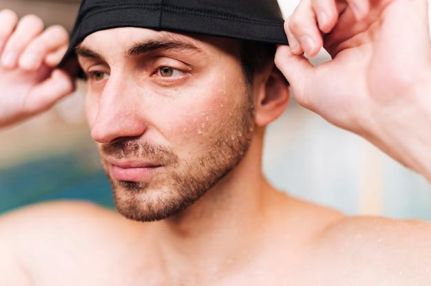 Junger mann der nahaufnahme, der auf badekappe sich setzt Kostenlose Fotos