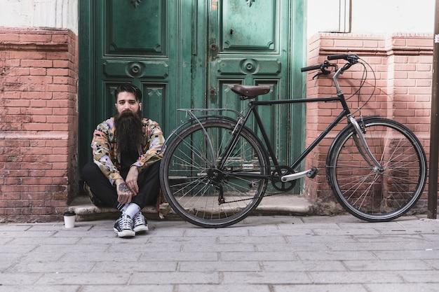 Junger mann, der nahe dem fahrrad mit mitnehmerkaffeetasse vor hölzerner grüner wand sitzt Kostenlose Fotos