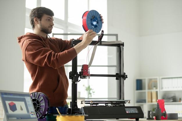 Junger mann, der neue spule mit rotem filament in 3d-drucker setzt, während geometrische figuren drucken Premium Fotos